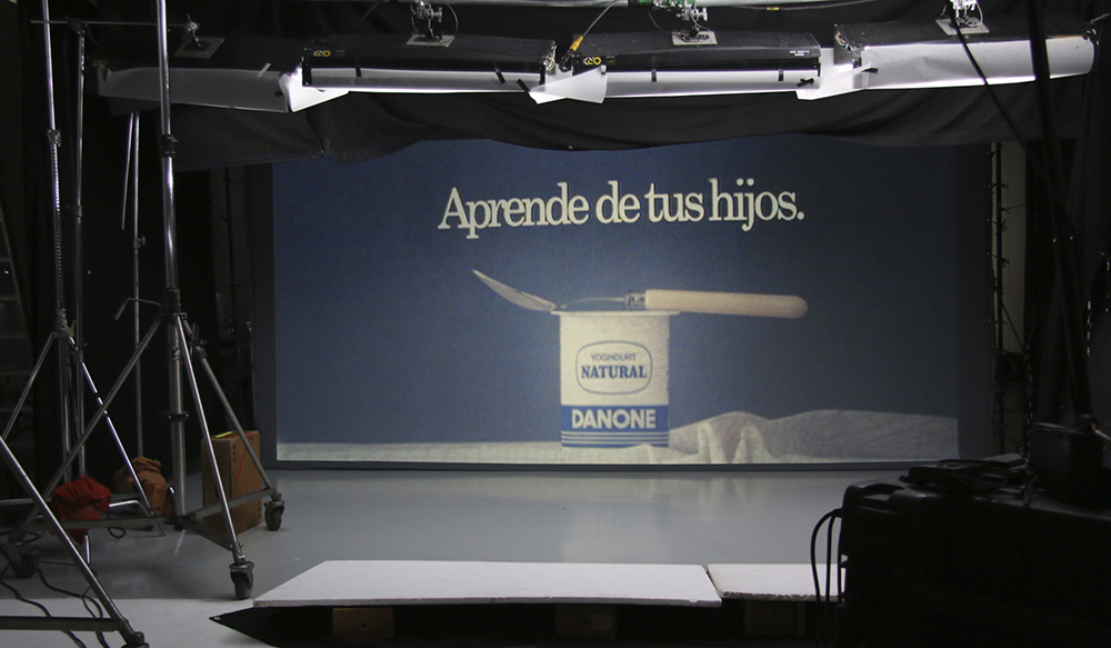 "Empty film set. In the center a canvas shows a giant frame with a plain Danone yogurt, a spoon and a text that reads, ""Learn from your children."""
