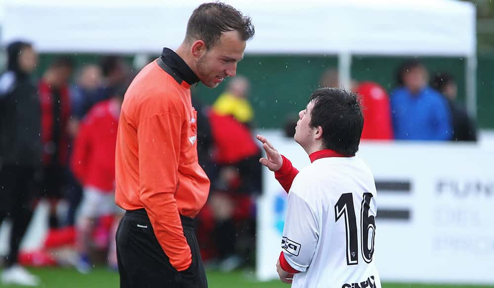 Footballer of the Liga Genuine, with learning disability, talking with a referee.
